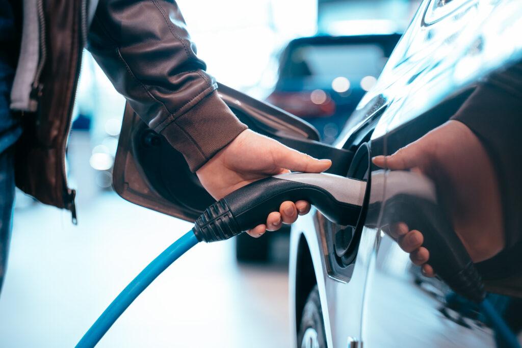 Mão recarregando carro em post de abastecimento de eletricidade